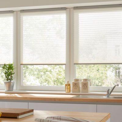 Verspannter Faltstore an einer Fensterreihe über einer Kochzeile