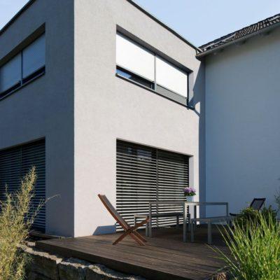 Rollladen bedecken die Fensterfront einer Hausfassade